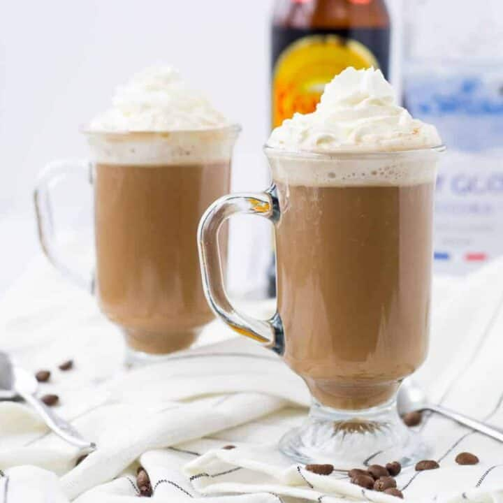 Front view of two clear glass footed mugs containing White Russian hot chocolate garnished with whipped cream.