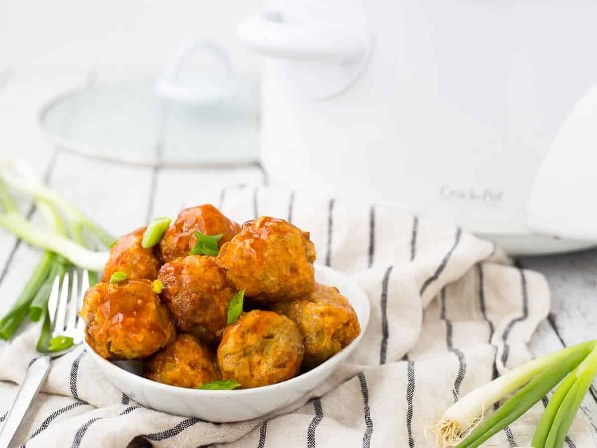 Small dish full of meatballs with crockpot in background.