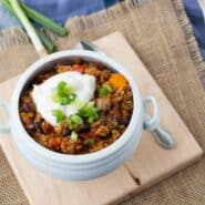 Quinoa chili in white bowl garnished with sour cream and green onions.