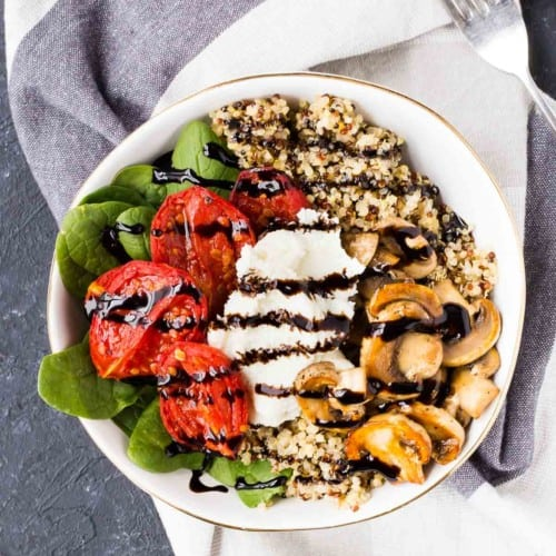 Overhead of shallow white bowl containing arranged salad with balsamic reduction drizzle.