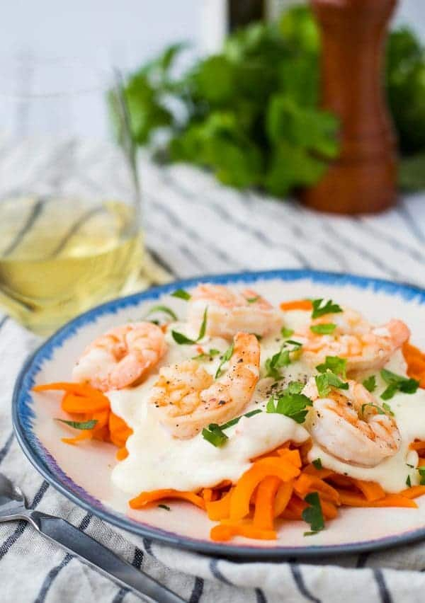 Blue rimmed plate with carrot noodles, alfredo, and shrimp, garnished with parsley. G