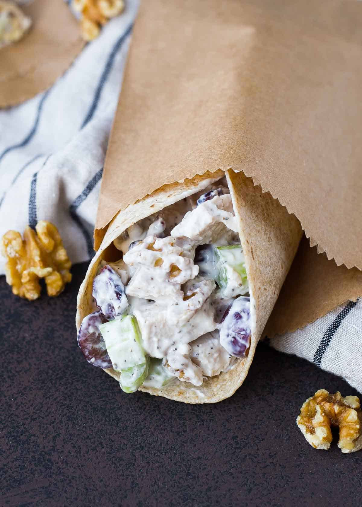 Chicken salad wrap partially contained in brown paper bag.