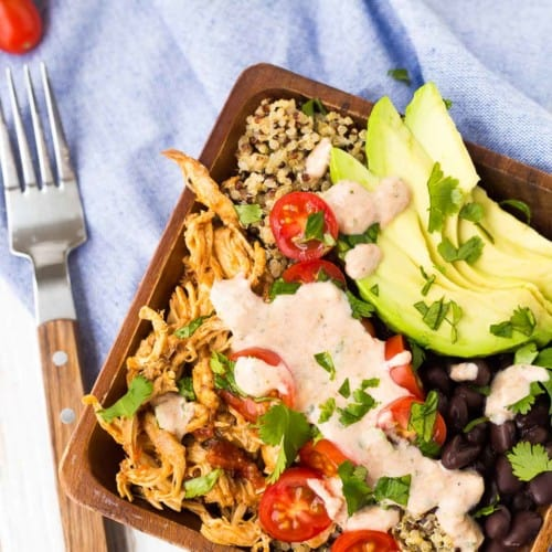 Partial image of quinoa bowl in square wooden salad bowl, with fork alongside.