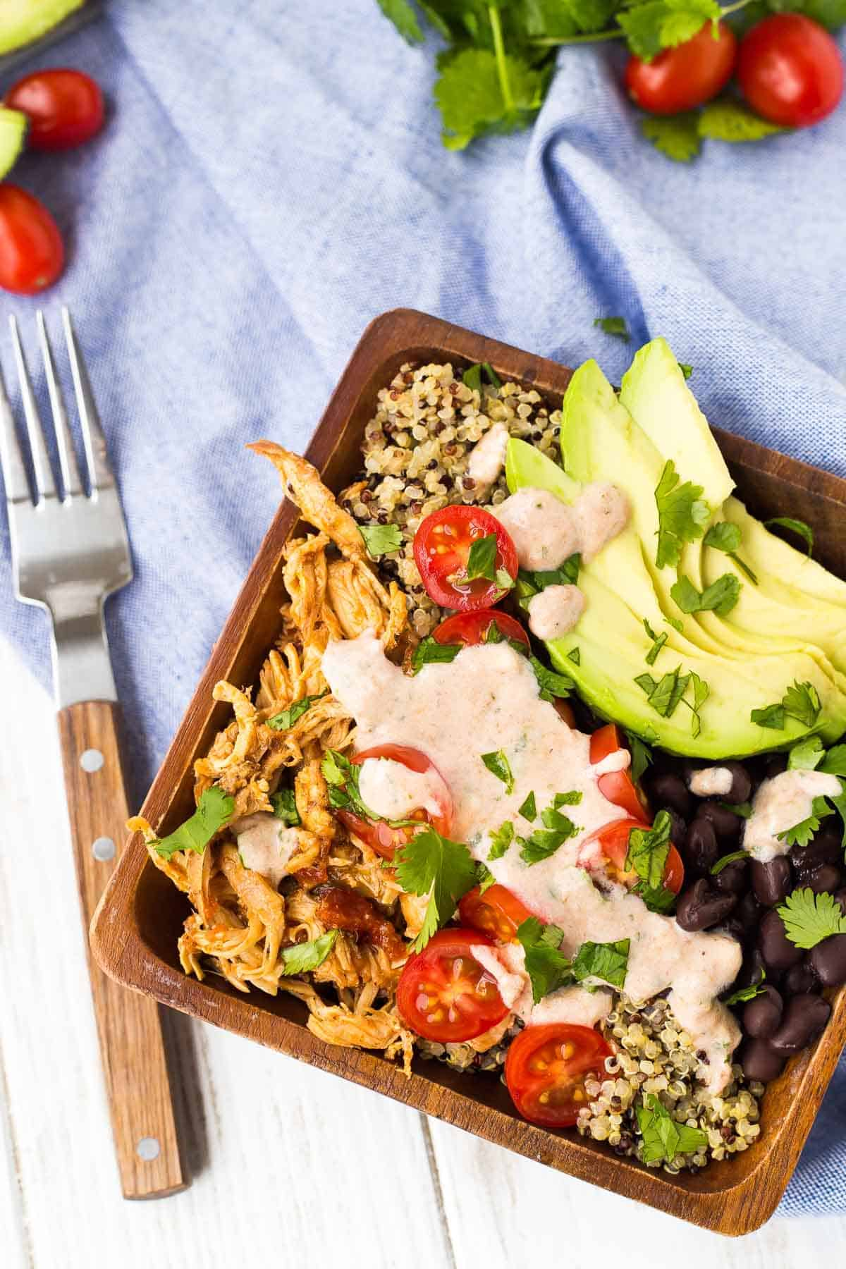 Overhead of southwestern quinoa bowl in square wooden bowl, with fork alongside.
