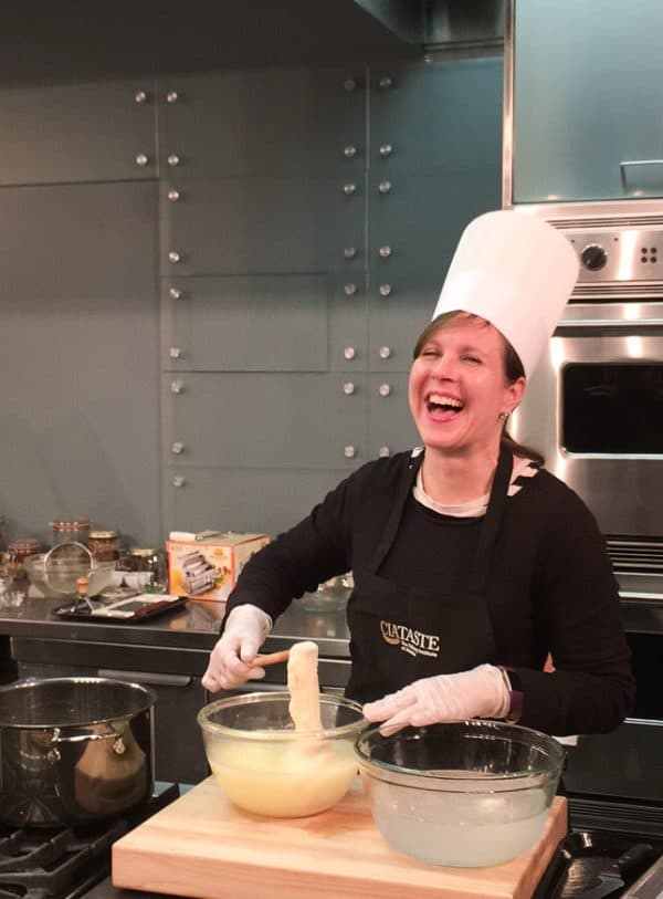 A woman, laughing, with a chef's hat on, as she makes fresh mozzarella.