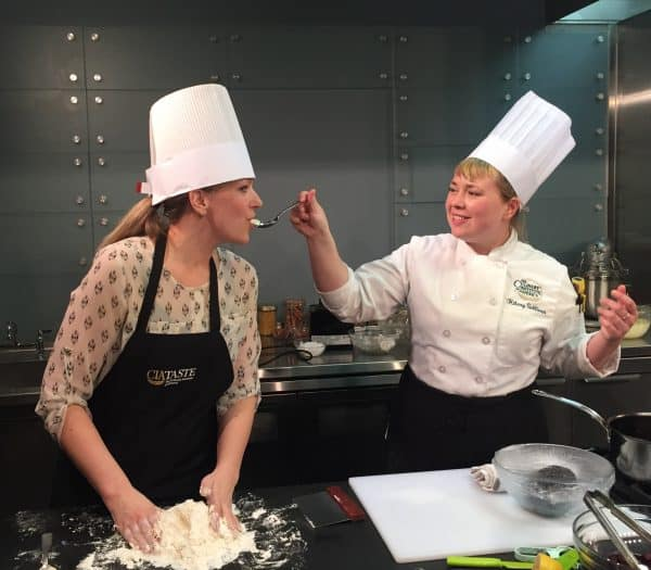 Two women wearing chef's hats and aprons, one is feeding the other as the one eating makes pasta with her hands.