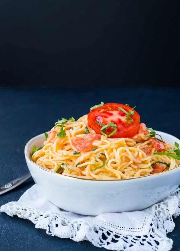 Image of a white bowl on a black background. Bowl is filled with angel hair pasta and a tomato cream sauce. It is garnished with a slice of tomato and fresh basil strips.
