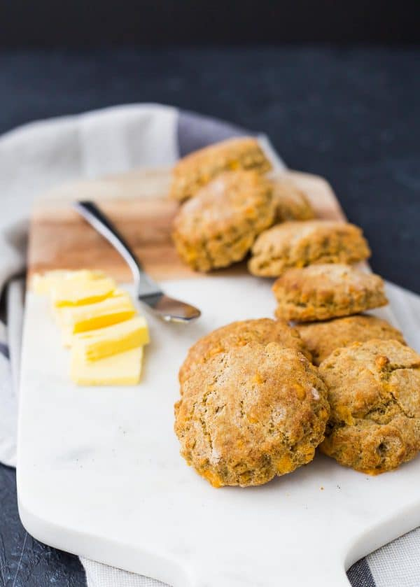 Several biscuits stacked on a white cutting board, with pats of butter and a spreader.