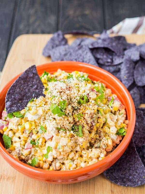 Mexican corn dip in orange bowl, surrounded with blue corn tortilla chips.