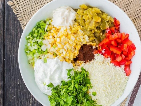 Overhead of skinny mexican corn dip recipe ingredients in shallow white dish.