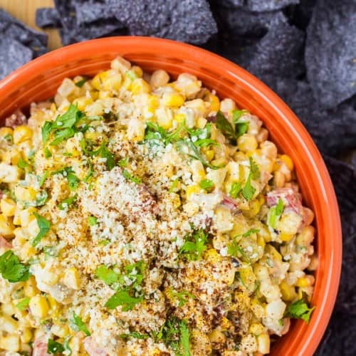 Corn mixed with cheese and cilantro in an orange bowl surrounded by blue corn chips.