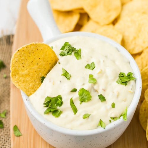 queso blanco with a chip dipped in and cilantro garnish
