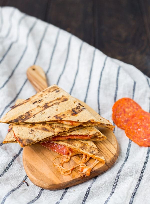 Quesadilla cut into quarters on small cutting board, with a couple pepperoni slices alongside.
