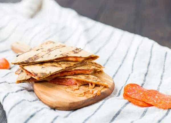Stacked quartered quesadilla on blue striped cloth.