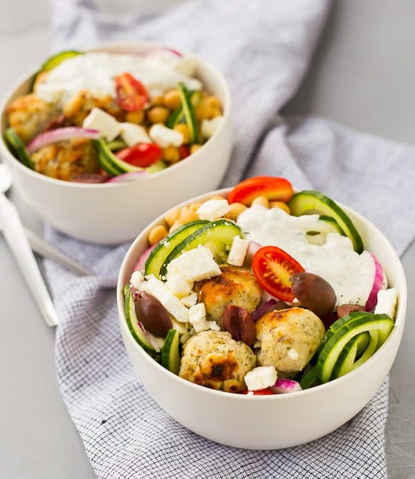 Two salads topped with meatballs in round white bowls.