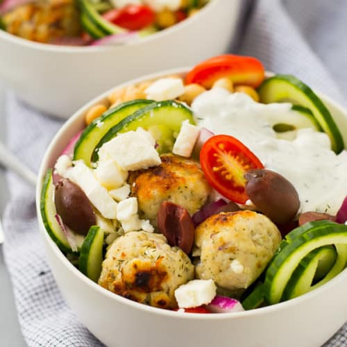 Salad in white bowl topped with greek meatballs and tzatziki.
