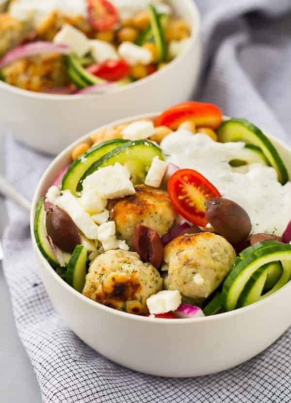 Salad topped with meatballs in round white bowls.