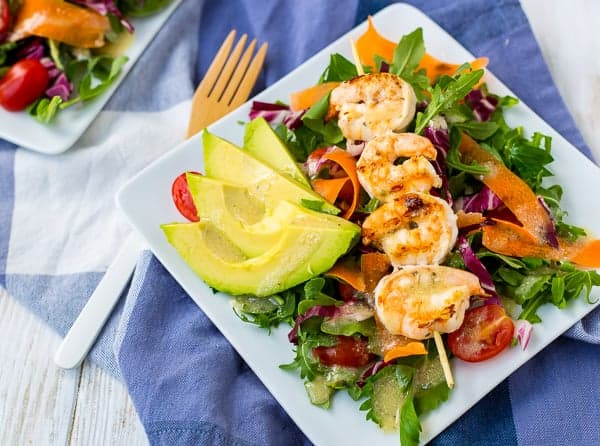 Grilled shrimp, on simple green salad with ribbons of carrot and sliced cherry tomatoes, garnished with sliced avocado.