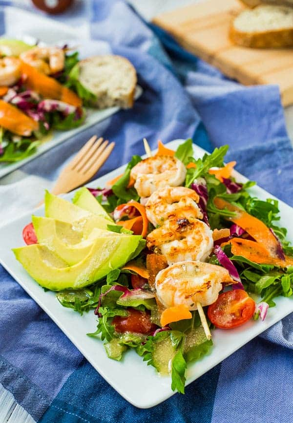 Plated shrimp salad on blue cloth, with sliced bread on wooden cutting board in background.