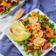 Grilled shrimp on skewer, served on salad and garnished with sliced avocado, on square white plate.