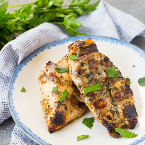 Two portions of grilled chicken on small blue rimmed white plate.
