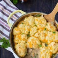 Overhead of Dutch oven containing chicken stew with cornmeal biscuits.