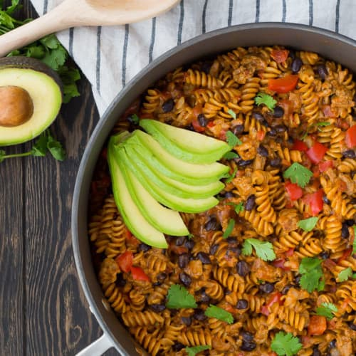 Overhead of taco pasta in deep skillet garnished with avocado and cilantro.