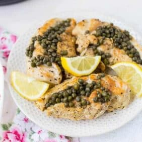 Cooked chicken on a plate with lemon slices and capers.