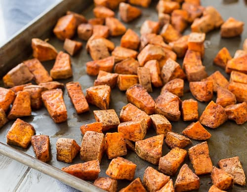 Partial image of sheet pan containing roasted sweet potatoes