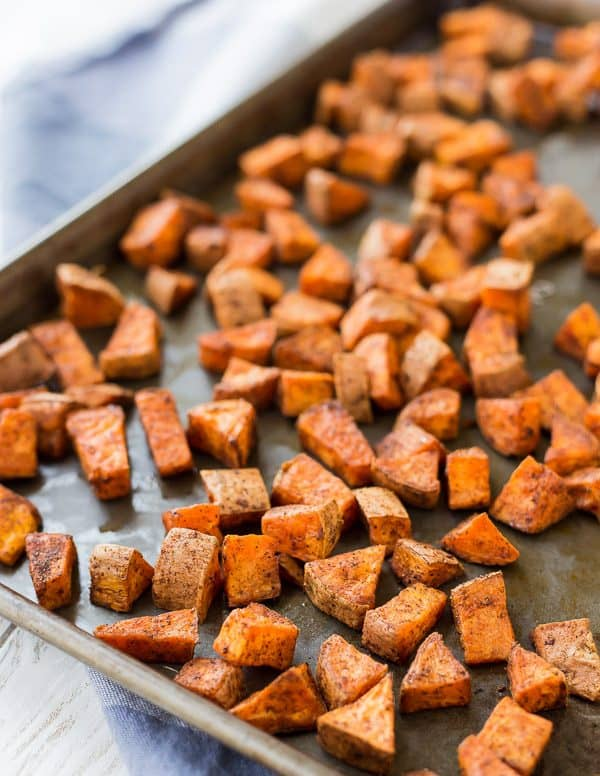 Partial view of sheet pan containing roasted sweet potatoes.