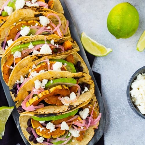Overhead of several prepared tacos, lined up on decorative surface.