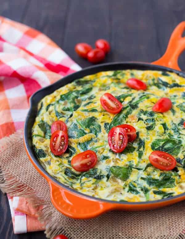 Egg frittata in an orange cast iron skillet on a wooden surface.