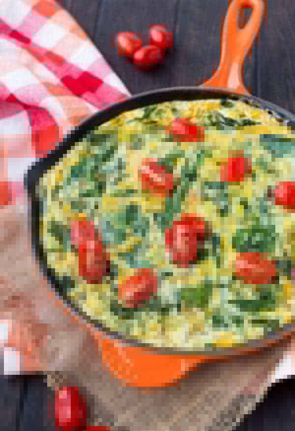 Frittata with spinach and tomatoes in an orange skillet.
