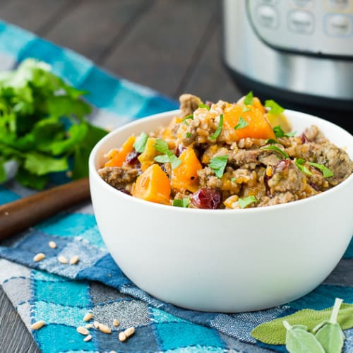 Farro stuffing in round white bowl garnished with fresh herbs.