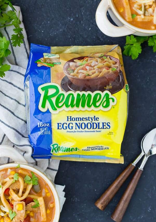 Front of a package of Reames Frozen Homestyle Egg Noodles, with filled soup bowls partially pictured.