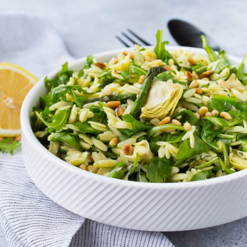 Partial front view of orzo salad in shallow white round bowl.