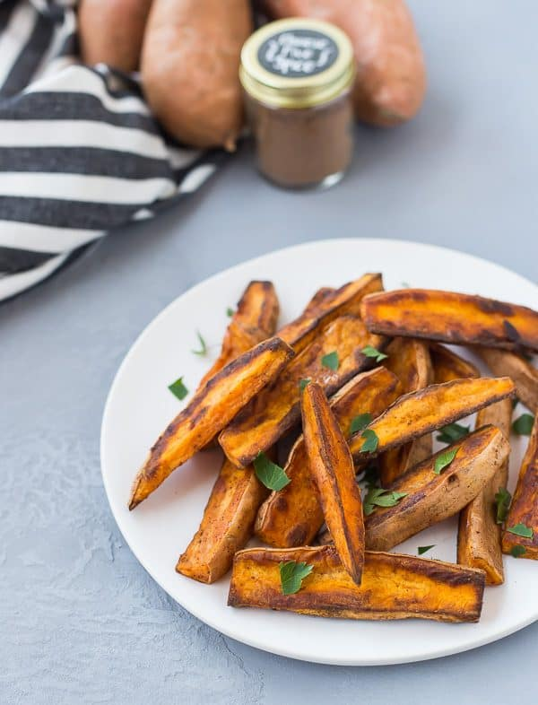 Plate of sweet potato wedges with jar of Chinese five spice and sweet potatoes in background.