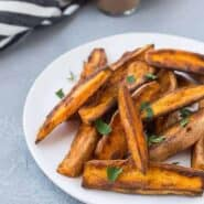 Sweet potato wedges on round white plate, garnished with chopped parsley.