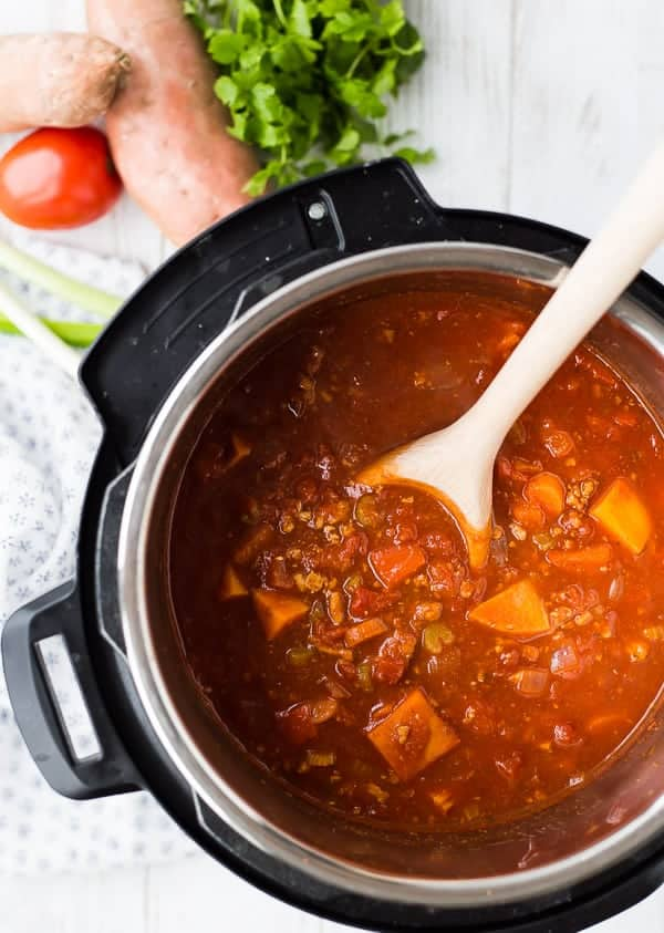 Overhead of chili in Instant Pot, with wooden spoon.