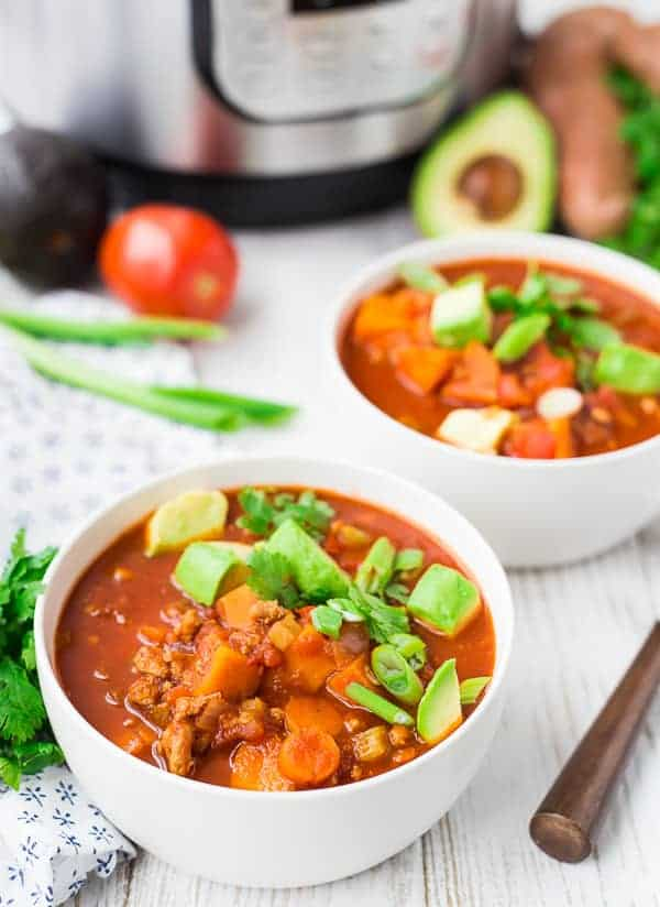 Two servings of chili in round white bowls, with spoon.