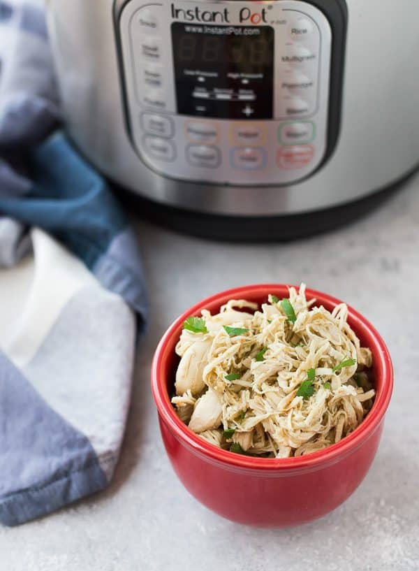 Small red bowl containing shredded chicken garnished with sliced green onions. Instant Pot in background.