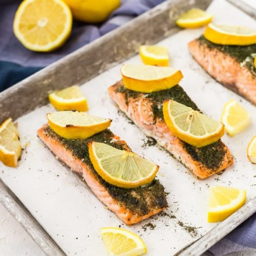 overhead of salmon in parchment lined sheet pan, with lemon slices.