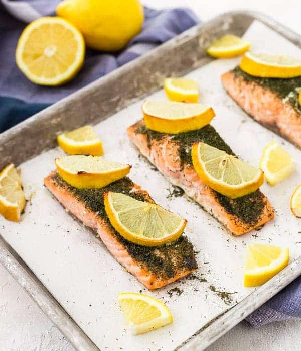 Overhead of salmon in parchment lined sheet pan, with lemon wedges.