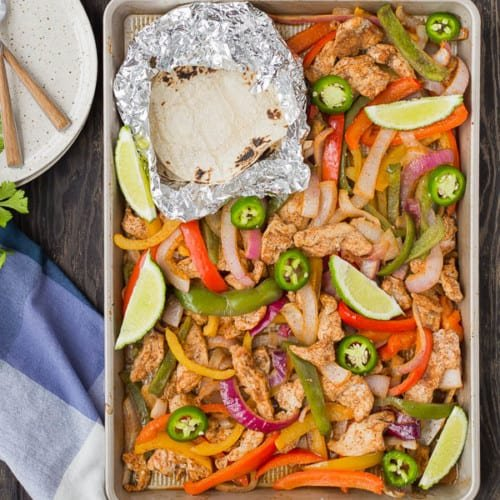 Overhead of sheet pan with baked chicken fajitas, and foil wrapped tortillas.