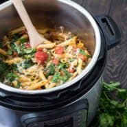 Pasta inside Instant Pot with wooden spoon inserted.