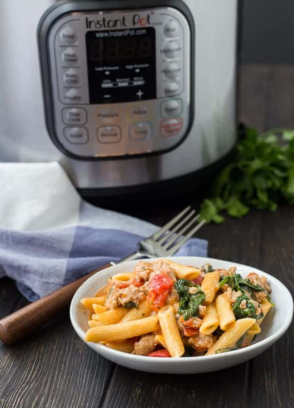 A serving of pasta in small white dish with fork. Instant Pot in background.