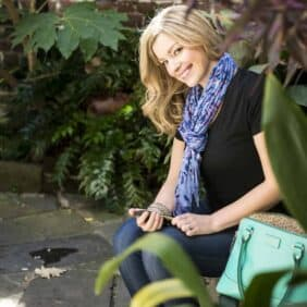 Blonde woman wearing a blue scarf, sitting on a bench holding a cell phone.