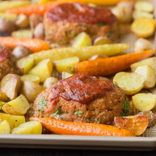 Mini meatloaves and roasted vegetables on sheet pan.
