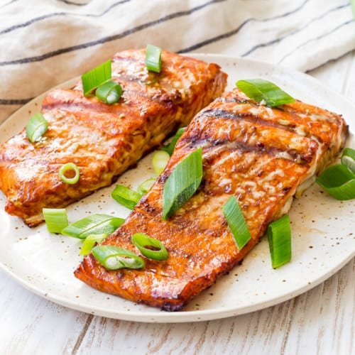 Two salmon fillets on a plate, sprinkled with bright green scallions.