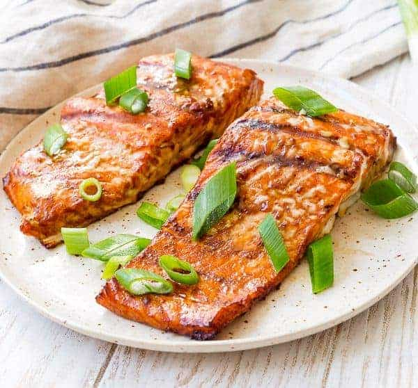 Close up view of salmon fillets on a natural colored, speckled plate. It is sprinkled with bright green scallions.